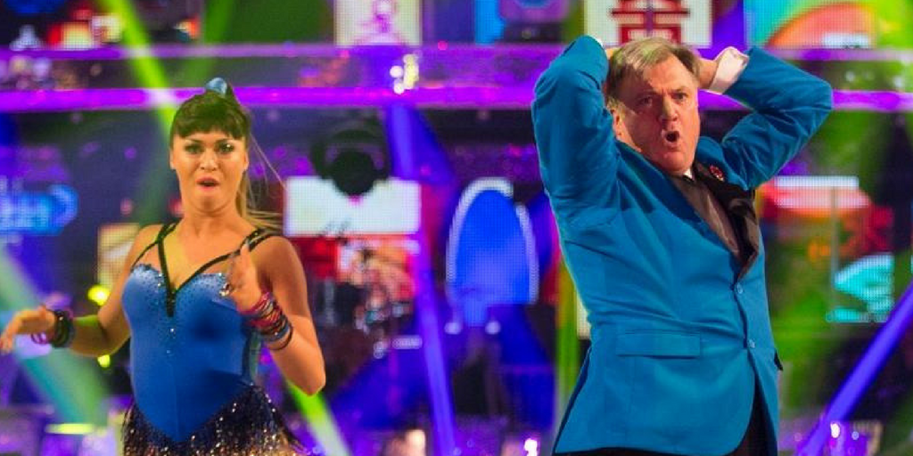 a woman and a man dancing wearing bright blue in a brightly lit studio
