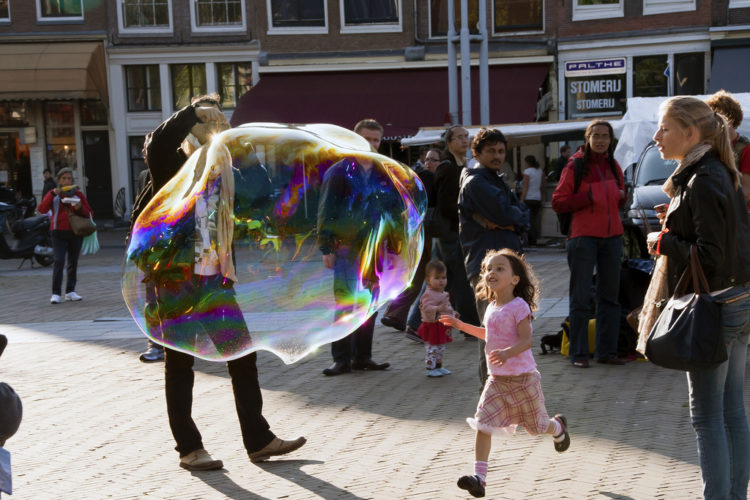 A man creates a huge bubble and a small girl runs towards it
